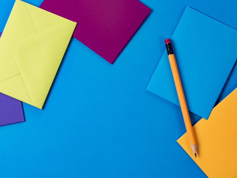 Photo: stationary scattered across a blue background and a pencil
