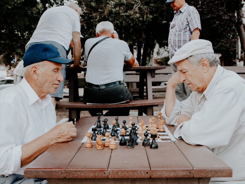 two elderly man sitting together and talking