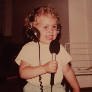 Photo: Michelle Seitzer as a young girl holding a microphone wearing headphones