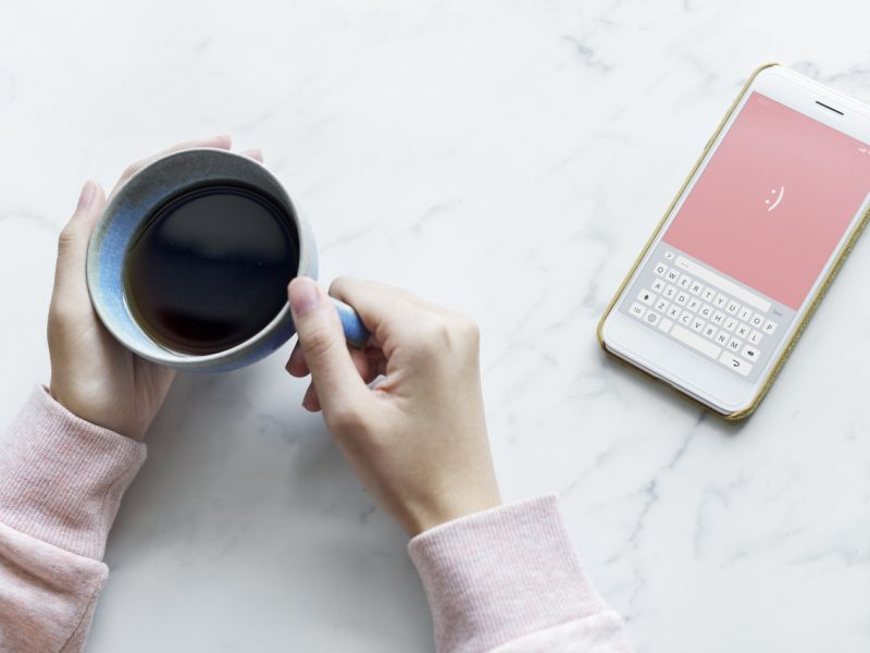 hands holding a cup of coffee with a phone nearby