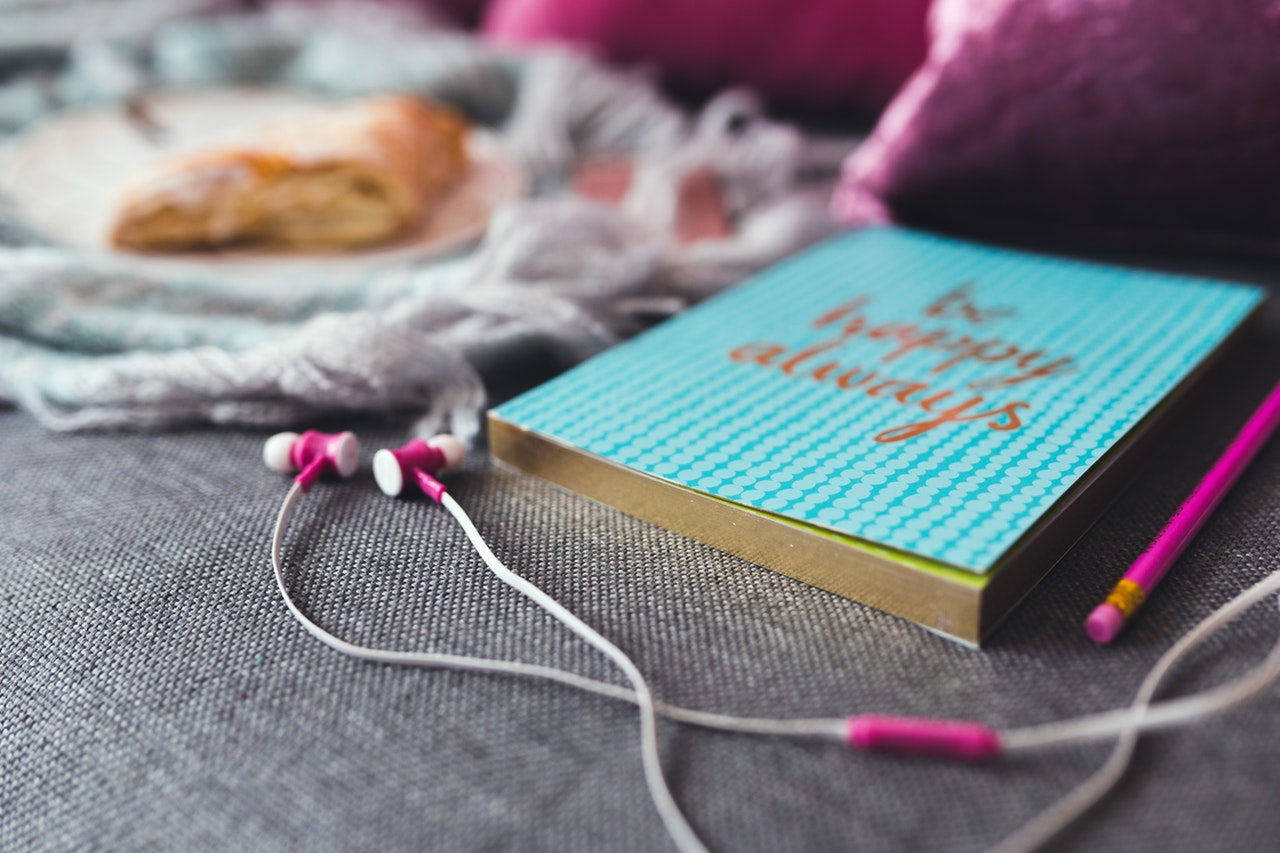 "Photo: ear buds laying next to a journal that says ""be happy always"" with a pastry in the background"