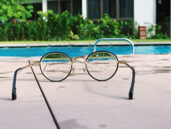 close up shot of a pair of glasses left on the side of a pool with the pool in the background