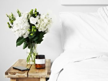 white sheets on bed with white flowers in vase on nightstand