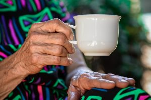 close up of older woman holding white coffee mug