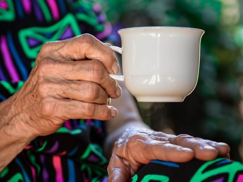 close up of older woman holding white coffee mug