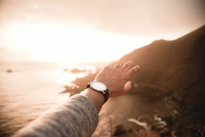 man's arm reaching towards sunset over the ocean with watch on wrist