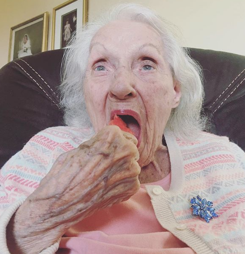 the author's grandmother sneaking a snack, sitting in an armchair