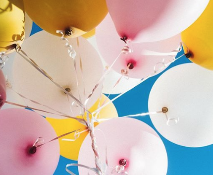 colorful balloons on blue background, taken from below