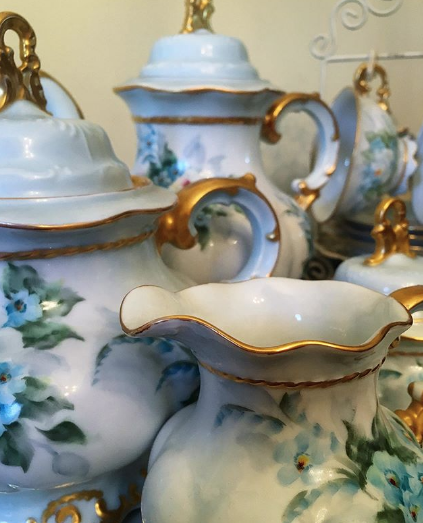 close up of beautiful tea pots, white with blue flowers and gold trim
