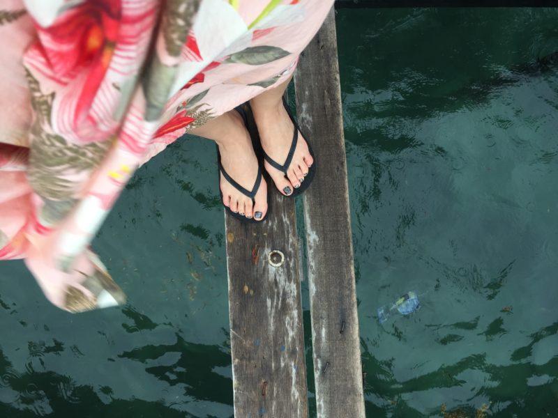 woman standing on bridge in flip flops and flowy flowered skirt, water below