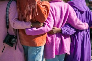 4 women standing together, photo taken from behind, arms around waists, bright purple, pink, and orange jackets