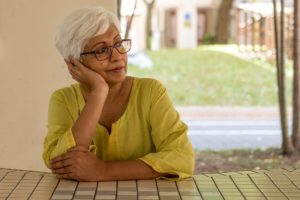 attractive older woman with short white hair and glasses sitting in front of window, looking out