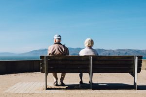 older adults sitting bench facing the sea